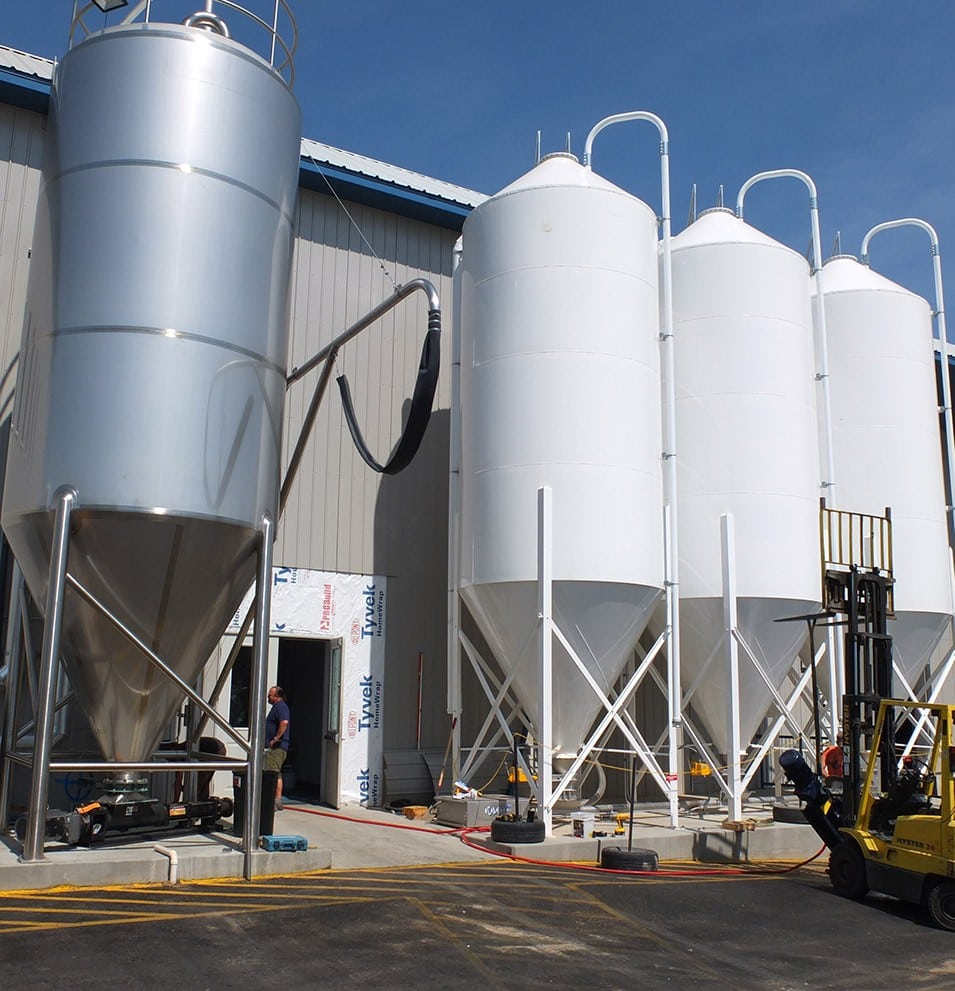 3 mild steel silos beside a stainless steel silo